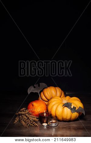 on a wooden floor are orange and yellow pumpkins in anticipation of Halloween, burning scented candles, drawings of black bats