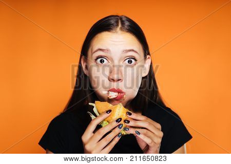 young beautiful girl wants to lose weight, but eagerly eats a large harmful hamburger,looks at the camera in surprise