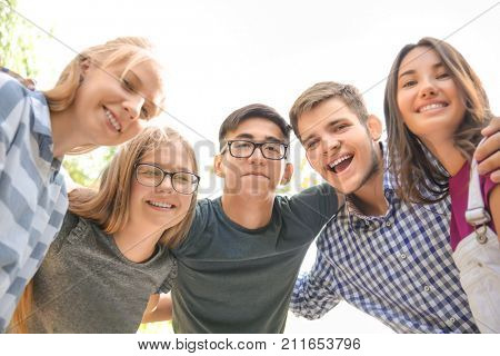 Happy teenagers hugging outdoors