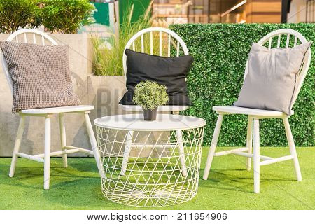 A Pillows on a white wooden chairs and a Artificial tree in pot on a white table on artificial grass.