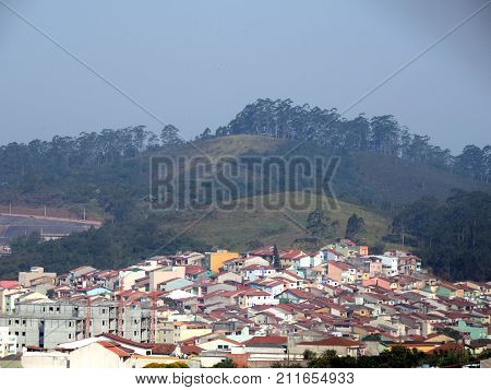 A town with many houses and the green hills on the background