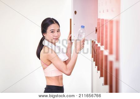 Asian woman pose and smiling putting water bottle in locker room of sports center and row of wood locker in the room