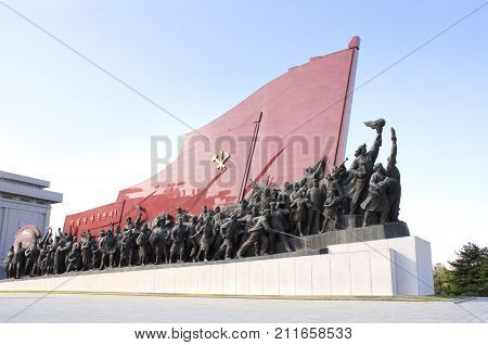 PYONGYANG, NORTH KOREA (DPRK) - SEPTEMBER 14, 2017: Grand Monument Mansudae. Statues of revolutionary people (men, women, children, soldiers, sailors, collective farmers, workers) with national flag
