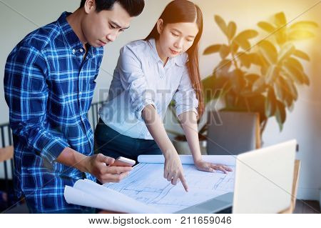 Construction designer and renovate concept. - Architects working with blueprints in the office. Confident team of young Asian engineers working together in a architect studio