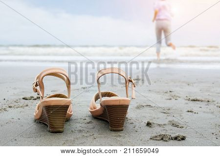 Beach holidays travel vacation lifestyle concept - Happy middle aged business woman take off shoe run into the sea with barefoot enjoying beautiful beach.