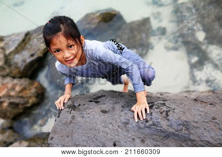 Asian girl children doing rock climbing with free hand.Training skills and practice extreme sports.