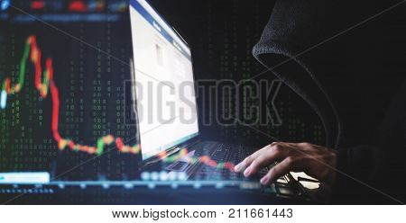 Internet crime and speculate stock concepts, Hacker working on computer laptop with downward stock graph background