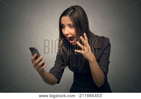Young stressed woman holding mobile phone in hands and unpleasantly surprised at what he sees on the screen.