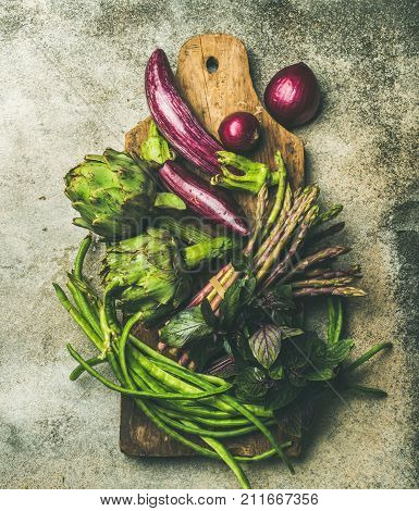 Flat-lay of green and purple vegetables on board over grey background, top view. Local produce for healthy cooking. Eggplans, beans, kale, asparagus, onions, artichoke, basil. Clean eating