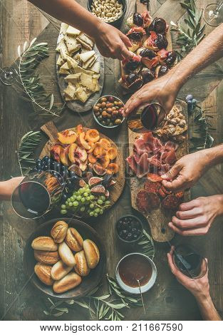 Flat-lay of friends hands eating and drinking together. Top view of people having party, gathering, dinner together sitting at wooden rustic table set with wine snacks and fingerfoods