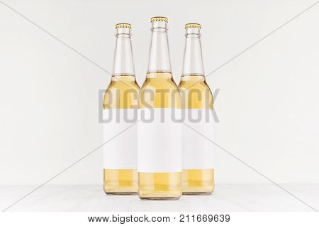 Three transparent longneck beer bottles 500ml with blank white label on white wooden board mock up. Template for advertising design branding identity.
