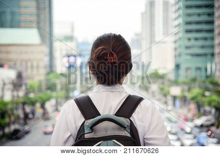 Challenge concept. Asian Woman in white shirt standing on the traffic jam and buildings background in the city.