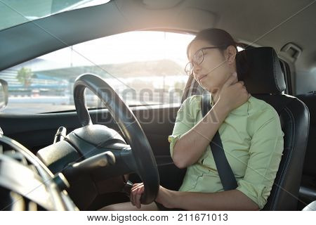 Asian glasses business woman having pain on her shoulder back and neck while driving a car. Illness exhausted disease tired for overtime working concept.