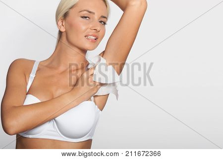 Higiene - young woman wiping the armpit with wet wipes perspiration sweat