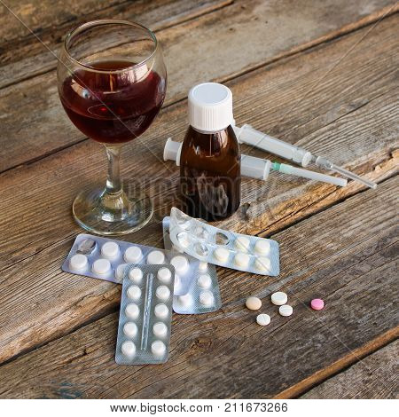 Medication and alcohol on the old wooden background.