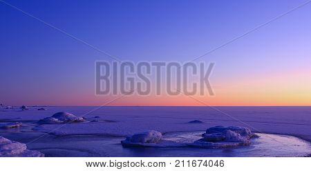 The Baltic Sea in late December, noon. Shore, shoreline, sea, ice and snow. Twilight.