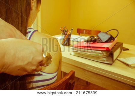 General practitioner doctor using a stethoscope to listen to a young patient's - Retro color