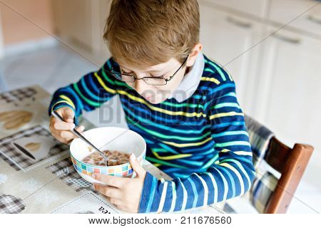 Adorable Happy little blond kid boy with glasses eating homemade cereals for breakfast or lunch. Healthy eating for children. At nursery, at school canteen or at home.