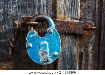 The old wooden door is closed by a rusty blue barn castle. Padlock on the garage door. Gate locked on the castle. Vintage, old. Storage room, garage, hangar.open lock, door breaking