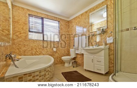 Brown and beige tiled modern bathroom with showerbath and hand basin in a luxury home