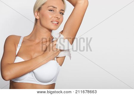 Hygiene - young woman wiping the armpit with wet wipes, perspiration, sweat