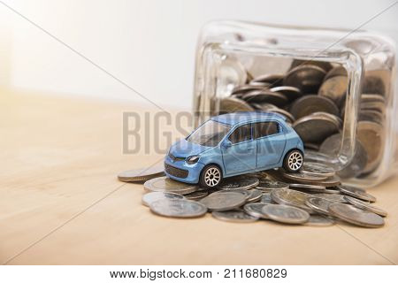 car with money coin on wood table. insurance concept.