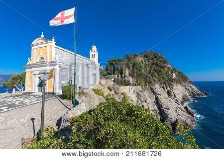 PORTOFINO, ITALY. October 20, 2017: Church of San Giorgio (Portofino). The church of San Giorgio is a Catholic worship site in Portofino, located on the San Giorgio slope. Rocky coastline and waves.
