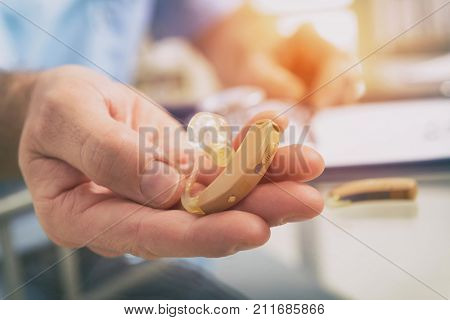 Doctor audiologist holding hearing aid in his hand