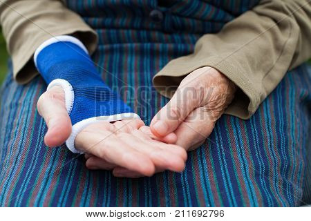 Close up picture of senior woman with blue elastic bandage on his wrist on isolated background