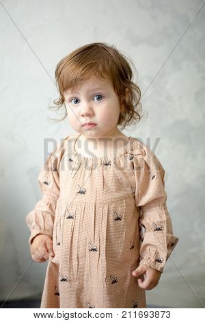 Portrait of little girl on gray background. Full cheeks, thick blond hair. Sweet girl with curly hair against a textured wall. The girl in pajamas.