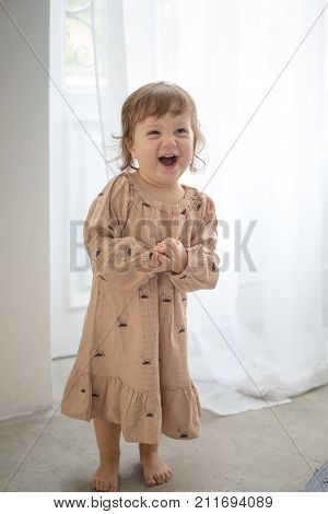 Portrait of happy little girl on gray background. Full cheeks, thick blond hair. Sweet girl with curly hair against a textured wall. The girl in pajamas.