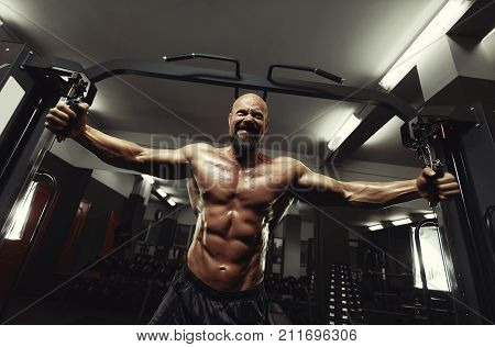 Low angle shot of a bearded shirtless muscular mature man working out on crossover cable machine at the gym brutality masculinity competitive bodybuilder ripped sexy hot body torso.