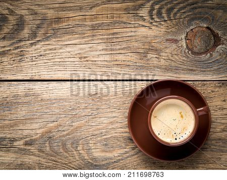Black Frothy Coffee With Foam In Brown Cup With Plate