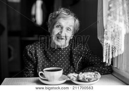 Elderly woman drinking tea at home.