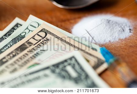 Money, drug, spoon and syringe with heroine on a table