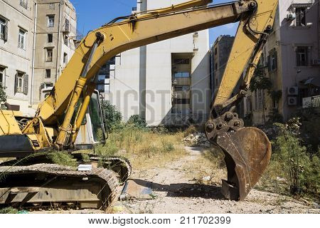 Yellow rusty Excavator parking in front of bulidings, Beirut, Lebanon