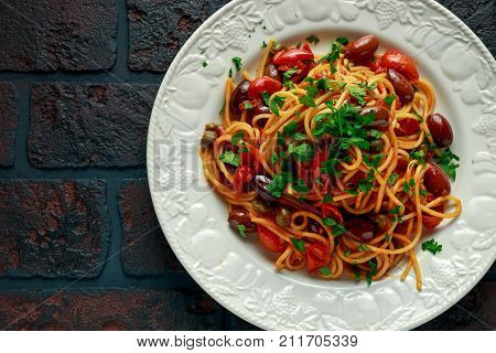 Vegetarian Italian Pasta Alla Puttanesca with garlic, olives, capers with on white plate