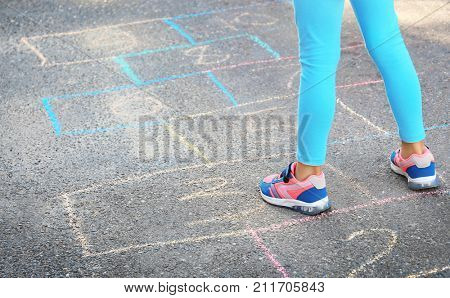 Child playing hopscotch outdoors