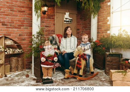 Young happy mother with cute little baby boy on rocking horse dressed in sweaters jeans and boots in decorated New Year studio. Christmas good mood. Lifestyle family and togetherness concept