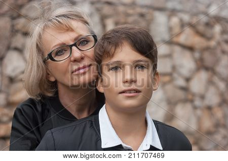 Good-looking single-parent mom and teen son in the park. Photo close up and copy space. Cohesion friendship and family relations.