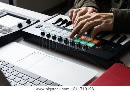 Recording electronic music track with portable midi keyboard on laptop computer in home studio. Producing and mixing modern style beats music beat making and arranging audio content with software controllers and digital effects processors