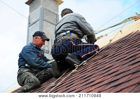 KYIV - UKRAINE NOVEMBER - 06 2017: Roofers install asphalt shingles. Contractors laying asphalt shingles and repair roof after hurricane damage.