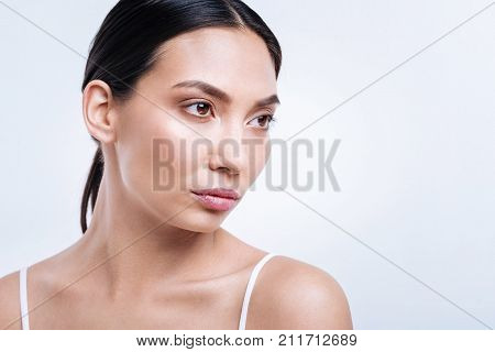 Menacing look. The portrait of a pretty dark-haired woman in tank top posing against a white background while looking into the distance with a displeased look