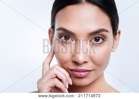 Mesmerizing look. The portrait of a charming dark-haired young woman touching her face with a finger while standing against a white background
