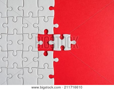 One white jigsaw puzzle beside missing jigsaw group on red background (Business Concept)