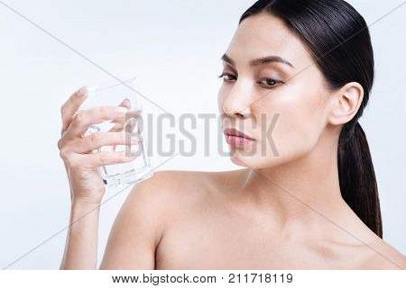 Staying hydrated. Charming dark-haired young woman with bare shoulders holding a glass of water and looking down while standing isolated on a white background