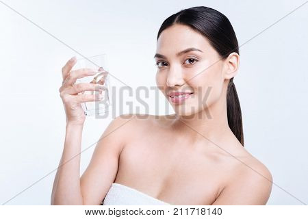 Sufficient water level. Beautiful dark-haired young woman holding a glass of water and smiling at the camera while standing isolated on a white background