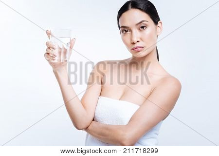 Stay hydrated. Charming young woman showing a glass of water to the camera while standing wrapped in a towel against a white background