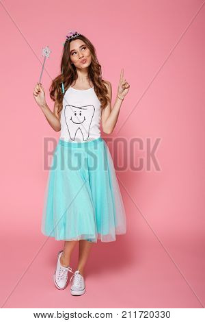Full length portrait of happy beautiful brunette woman dressed like princess holding magic wand, pointing with finger upward, isolated on pink background