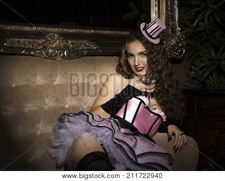Sexy cabaret woman in corset posing in vintage armchair. Burlesque lingerie in fashion interior.